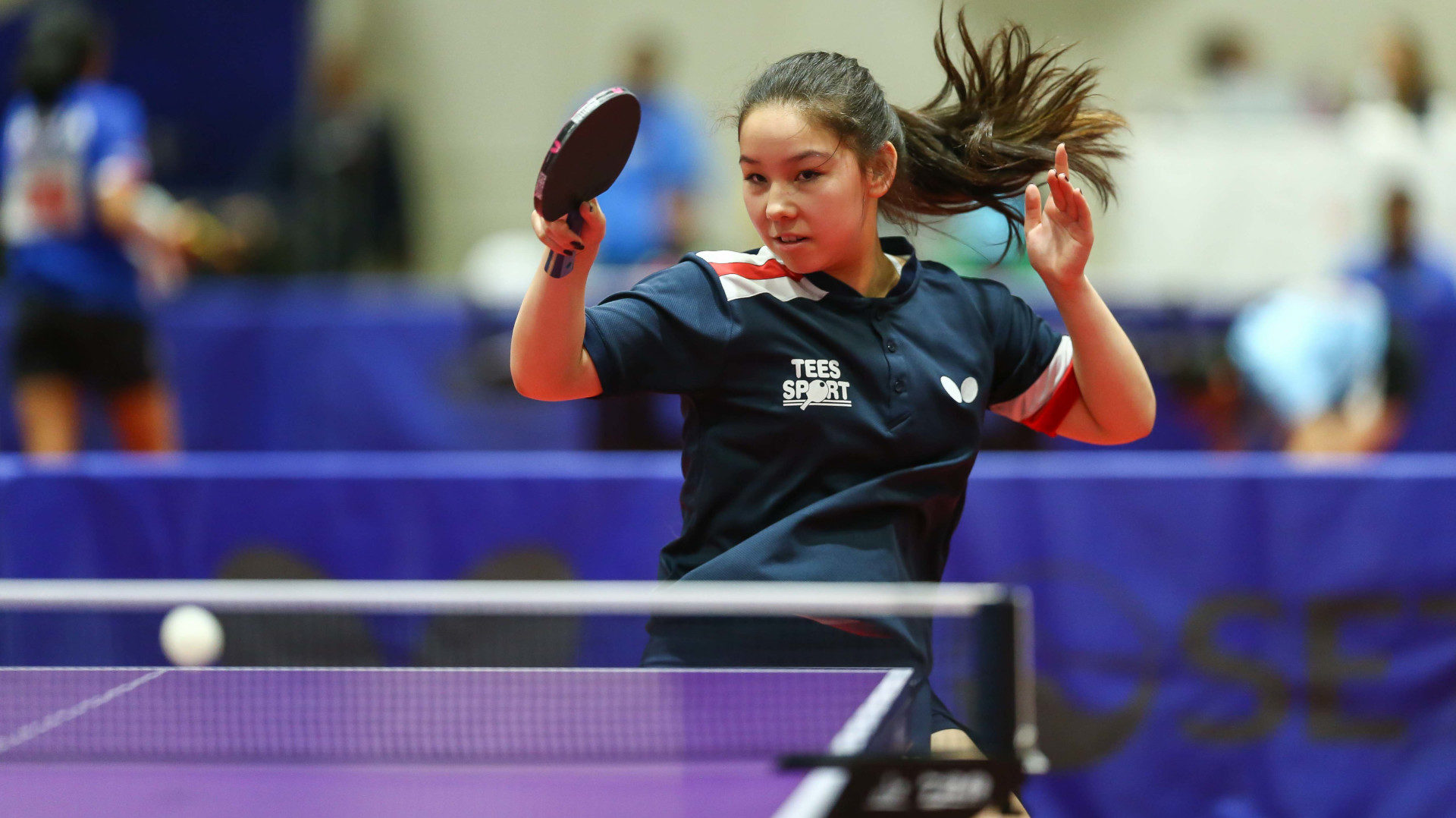 Teenage girl in action playing table tennis