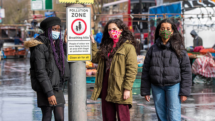 Young people standing next to a pollution zone sign