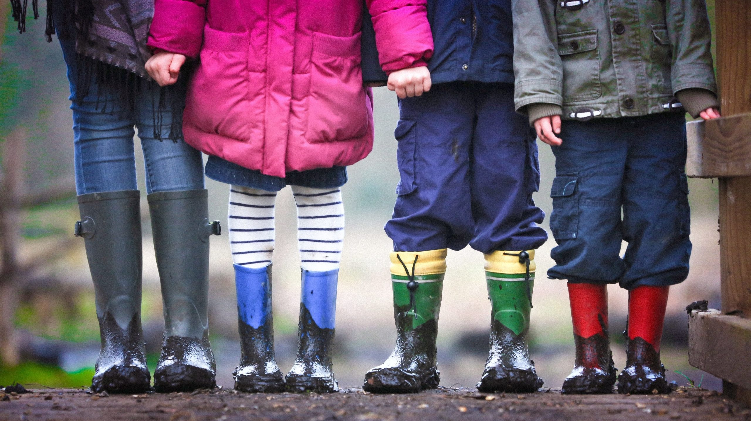 Children stand in a line in wellington boots