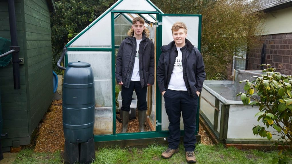 Two teenage boys stand in front of a greenhouse in a garden