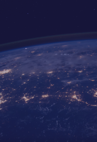 A night time view of the earth from space with cities lit