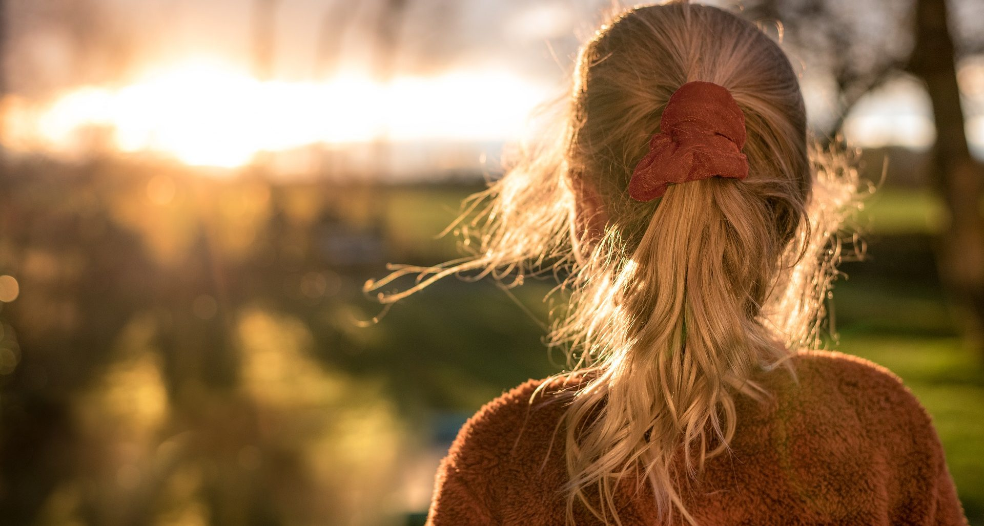 Girl with aponytail looks towards a sunset